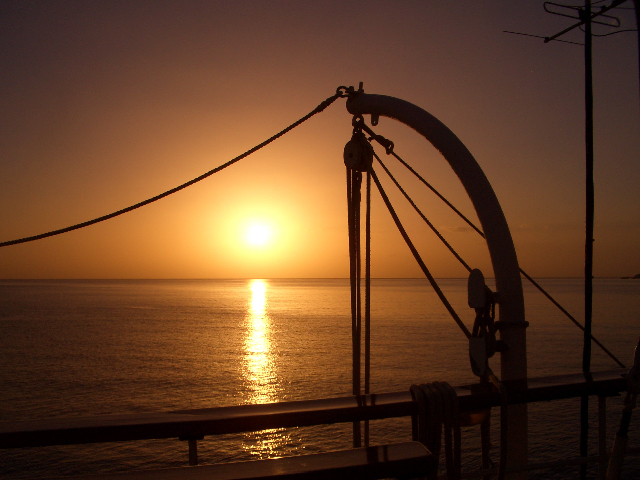 sun setting off the railing with the davits that hold up the launches in the foreground
