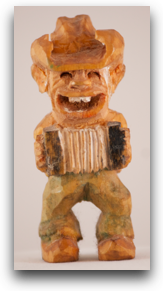 5cm tall carving my dad made of a little cowboy with an accordian and a cowboy hat and buck teeth