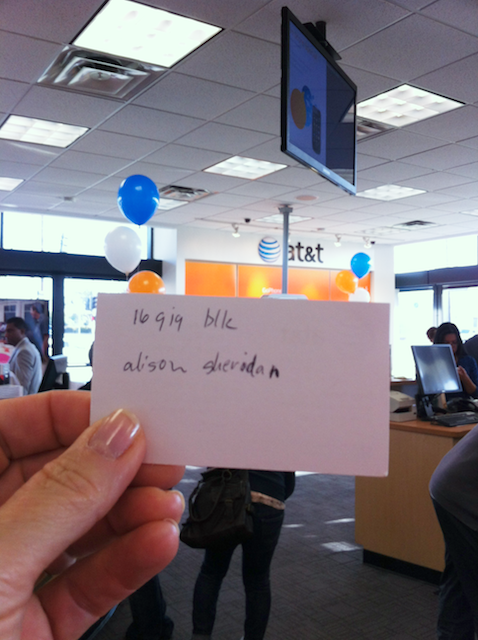 holding the golden ticket for my iPhone with the AT&T sign in the background