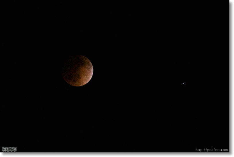 blood moon showing red, glowing more from the right than the left. Spica star to the right